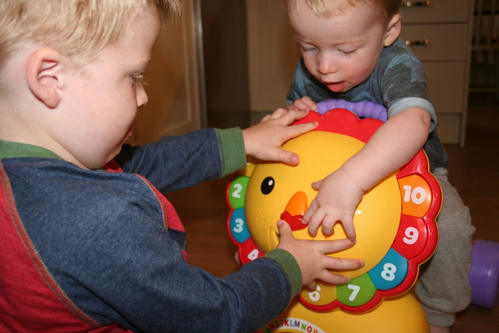 fisher price 3-in-1 sit, stride and ride lion review toby and teddy playing with the nose and numbers