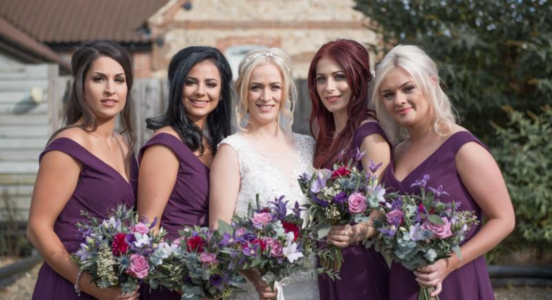 raising the rings wedding ronald joyce estella design ivory wedding dress mori lee aubergine dark purple bridesmaid dresses with purple bouquet of flowers